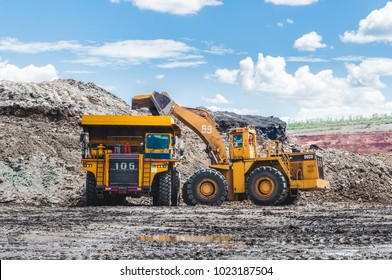 Excavator loading of coal, ore on the dump truck. The big dump truck is mining machinery, or mining equipment to transport coal from open-pit or open-cast mine as the Coal Production.