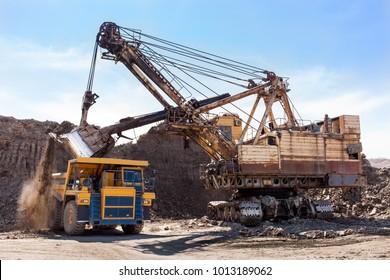 Excavator loading dump truck at coal mining