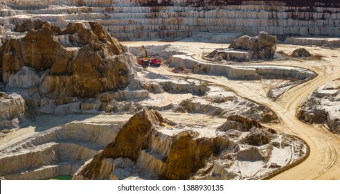 excavator loading dump truck with raw kaolin in kaolin open pit mine, Vetovo village area, Bulgaria.