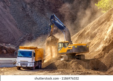 Excavator is loading excavation to the truck. Excavators (hydraulic) are heavy construction equipment consisting of a boom, dipper (or stick), bucket and cab on a rotating platform.