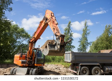 excavator loading ground to tipper truck on the street reconstruction site.