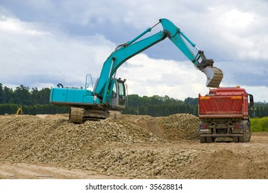 Excavator loading sand or rocks in lorry