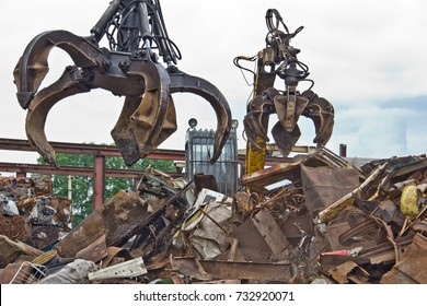 Excavator is loading scrap metal junk into a bin at a garbage dump or recycling center.
