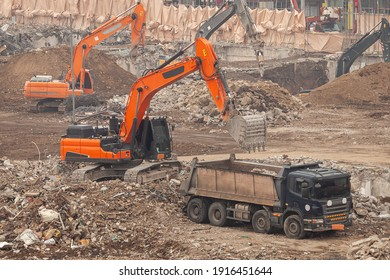 An excavator is loading something into a truck at the construction site.