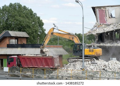 Excavator loads construction waste into the truck. Excavator bucket pours debris into the back of a truck. Destroyed house, concrete, fittings. The roadway.