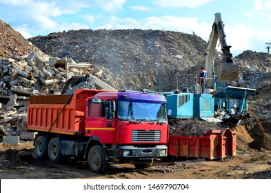 Excavator loads construction waste into reinforced concrete mobile shredder for crushing, recycling of construction mixed waste. Broken concrete recycling at industrial landfill. Screening plant