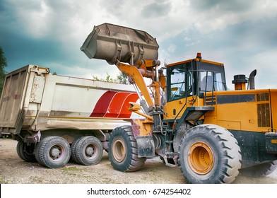 excavator loads gravel in truck