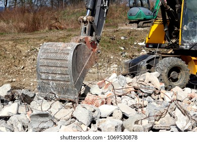 The excavator loads the load on the car. Construction works. Technology of urbanization. Heavy industrial machines. Building of the city. Mechanization of heavy manual labor. Modern technologies.