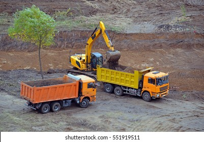 Excavator loads a truck dump soil dug from the construction pit