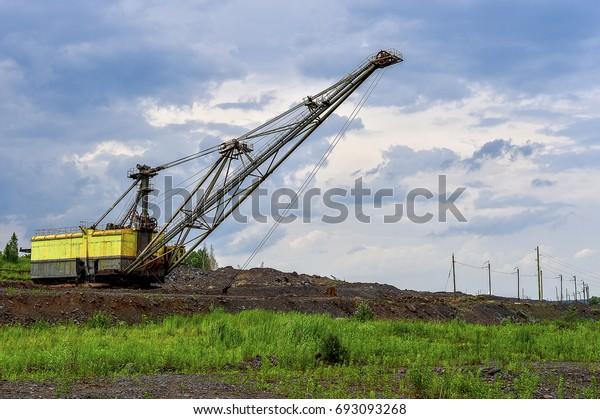 Excavator machine at excavation earthmoving work in quarry.