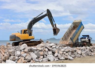 La máquina de excavación mueve la piedra con el cubo elevado al camión
