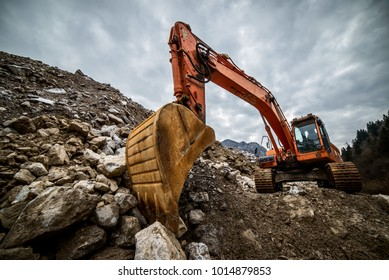 excavator is making pile of soil by pulling ground up on heap at construction site, project in progress.