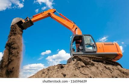 Excavator with metal tracks unloading soil at construction site during earthmoving works