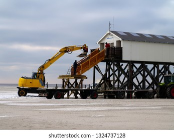 excavator mounting wooden parts on a beach building