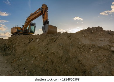 Excavator moving dirt and sand at a construction site