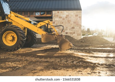 Excavator moving earth with the shovel on the construction site