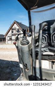 Excavator and newly built houses on construction site
