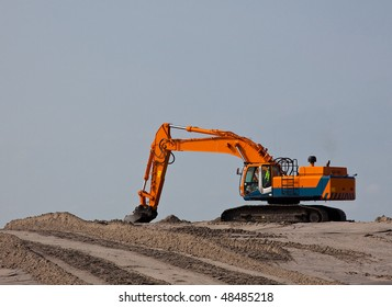 an Excavator on the beach on a dredging project in holland