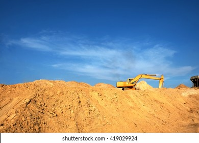 Excavator on big sand heap at construction site, background of the blue sky and sun.
