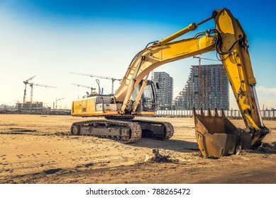 Excavator on construction site with bulldings in background,selective focus