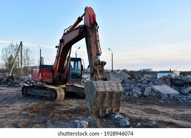 Excavator on demolition the old building. Backhoe the destruction of concrete and hard rock. Recycling of construction waste at the construction site