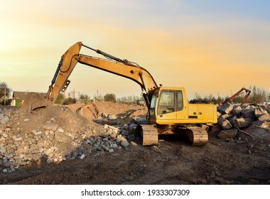Excavator on demolition the old buildingon sunset background. Backhoe the destruction of concrete and hard rock. Recycling of construction waste at the construction site