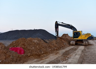 Excavator on earthworks at construction site. Backhoe on earthmoving and foundation work. Heavy machinery and equipment. Soft focus