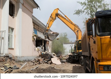 Excavator on wheels do the loading of construction debris and debris of the walls of the old building after the destruction, in the body of a dump truck