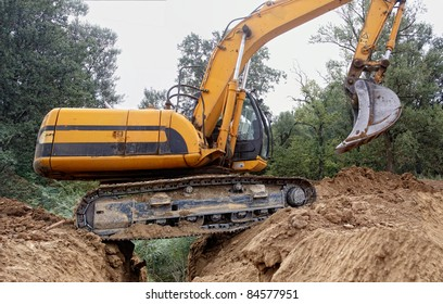 Excavator passes over a deep trench