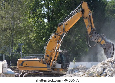 Excavator performs demolition work on an old hall