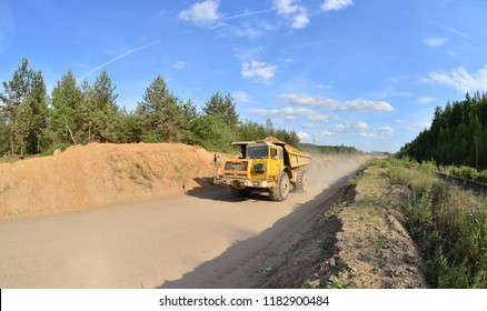 Excavator pours soil into the truck. Work truck in the quarryon transportation of sand. Extraction of minerals. Dump truck loaded with clay Belaz. Belarus