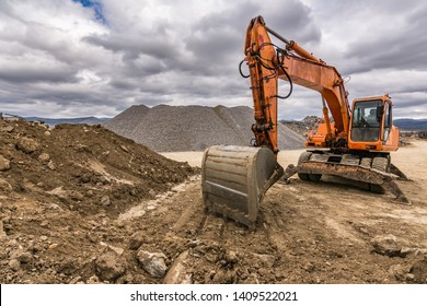 Excavator in a quarry extracting stone