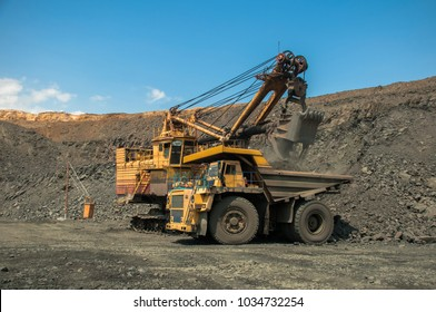 Excavator in the quarry loads the dumper with iron ore.