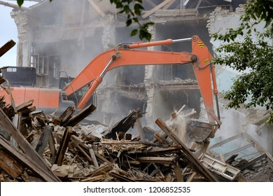 excavator rake the fallen building, debris is collected by bucket, a destroyed building