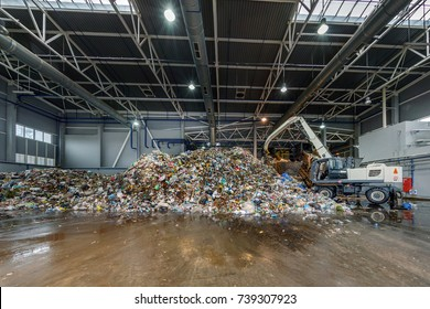 Excavator rakes a garbage heap at the waste processing plant. Separate garbage collection. Recycling and storage of waste for further disposal. Business for sorting and processing of waste.