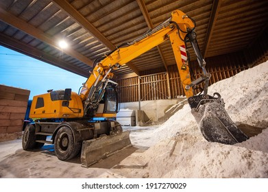 An excavator in a salt storage used for anti skidding on a road.