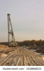A dragline excavator in a sand quarry. Phosphorite Mine. Tire tracks on a sand