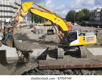 Excavator scooping mud on a urban construction site