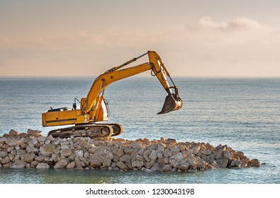 Excavator shifts stones on the beach.