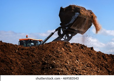 Excavator shovel working on a large heap of manure, organic fertilizer for the field, blue sky, copy space