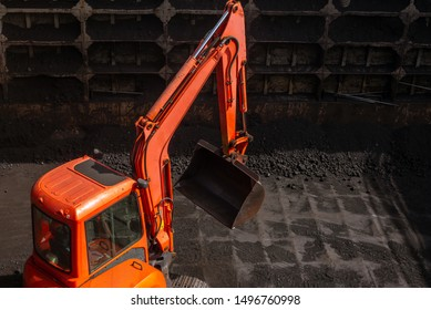 Excavator in a small barge vessel while discharging coal