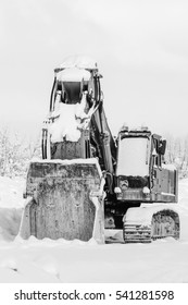 Excavator standing in the snow outdoors in winter, close up. The concept of unemployment problem. Black and white photo