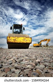 Excavator and steamroller on gravel road construction