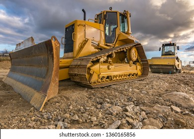 Excavator and steamroller work in the realization of a road
