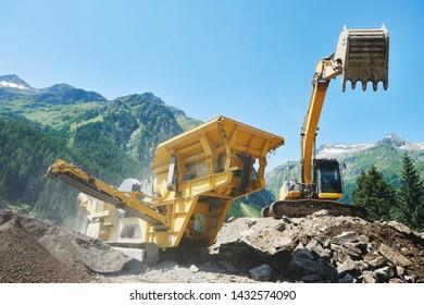 excavator and stone crusher machine. scalper at work