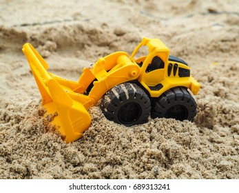 The excavator toy on the beach working with sand.