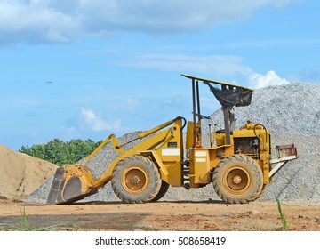 excavator or tractor or yellow loader park at a construction with rock sand sky background