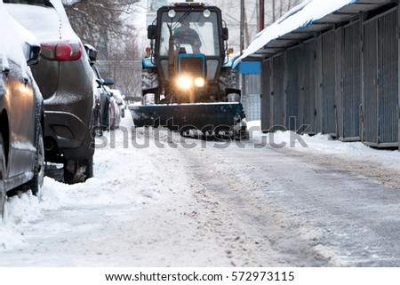 excavator and truck, clean the snow from roads and sidewalks in winter