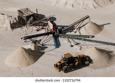 Excavator truck collecting gravel sorted by size in quarry
