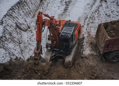 excavator and truck winter working hard in snow frozen ground